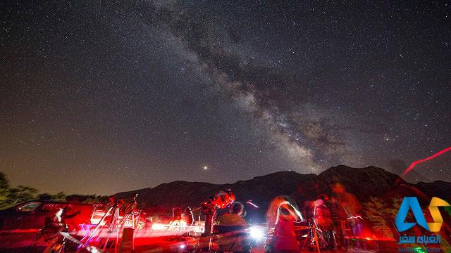 آسمان پر ستاره شب و افراد در حال رصد ستاره ها