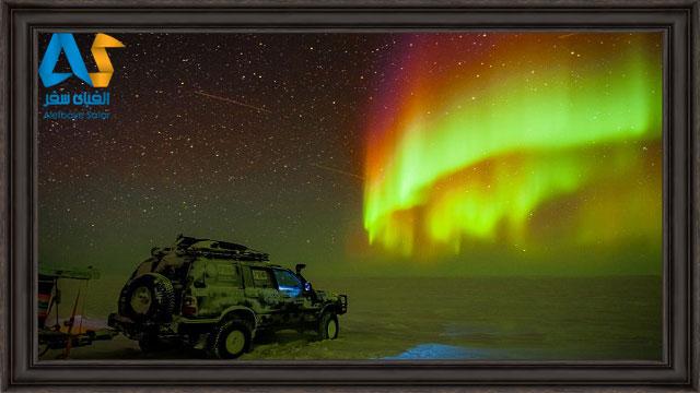 خودروي در برف و گردشگران در حال تماشاي شفق هاي قطبي روسيه