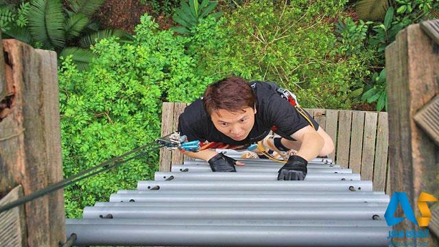 فردي در حال بالا رفتن از نردبان يكي از قسمت هاي مجموعه تفريحي ورزشي اسكاي تركس